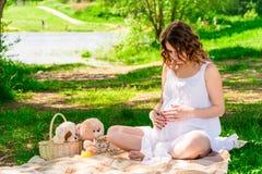 Fille enceinte dans l'attente de parc Images stock