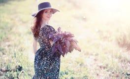 Fille enceinte dans un domaine avec des fleurs photo stock