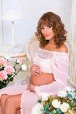 Fille enceinte de roux s'asseyant sur la chaise et étreignant le ventre avec amour Images libres de droits