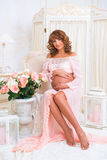 Fille enceinte de roux s'asseyant sur la chaise et étreignant le ventre avec amour Image libre de droits