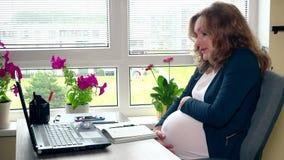 Fille enceinte fatiguée s'asseyant près du grand ventre d'ordinateur et de course clips vidéos