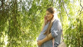 Fille enceinte Femme enceinte en stationnement Femme parlant au téléphone banque de vidéos