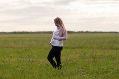 Fille enceinte marchant dans la nature et le sourire Photographie stock