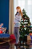 Fille enceinte mignonne dans la robe grise sur le fond du ch Photos libres de droits