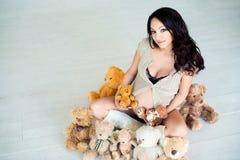 Fille enceinte s'asseyant sur le plancher chaud avec des ours de nounours Photo stock