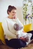 Fille enceinte s'asseyant sur un lit et tenant le jouet dedans Images stock