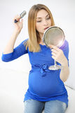 Fille enceinte se brossant les cheveux Photo stock
