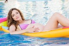Fille enceinte sur le matelas dans la piscine de swimmimg Photo libre de droits