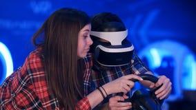 Fille ennuyée essayant de distraire son ami de jouer la réalité virtuelle emballant le jeu Photo libre de droits