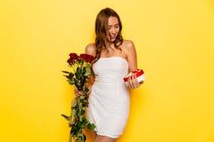 Fille enthousiaste avec les roses et le boîte-cadeau célébrant le jour du ` s de Valentine Images libres de droits