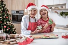 Fille enthousiaste célébrant Noël avec sa grand-mère Image libre de droits