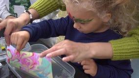 Fille enthousiaste de fille avec la mère faire la peinture d'ebru sur l'eau Mouvement de cardan clips vidéos