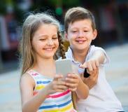 Fille enthousiaste et garçon regardant des téléphones portables en parc Photo libre de droits