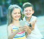 Fille enthousiaste et garçon regardant des téléphones portables en parc Photos libres de droits