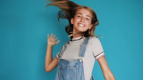 Fille enthousiaste heureuse avec de longs cheveux sautant avec des mains augmentées La belle fille saute et rit du bonheur Portra banque de vidéos