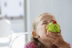 Fille enthousiaste mangeant le petit gâteau photo stock