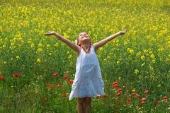 Fille entourée par des fleurs de graine de colza Photo stock