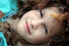 Fille entourée par des lames d'automne Photographie stock