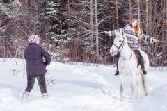Fille, entraîneur de cheval et cheval blanc en hiver Photographie stock libre de droits