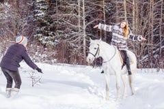 Fille, entraîneur de cheval et cheval blanc en hiver Images libres de droits