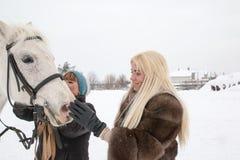 Fille, entraîneur de cheval et cheval blanc un hiver Photo libre de droits