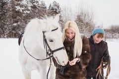 Fille, entraîneur de cheval et cheval blanc un hiver Image stock