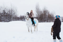 Fille, entraîneur de cheval et cheval blanc un hiver Photographie stock libre de droits