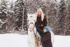 Fille, entraîneur de cheval et cheval blanc un hiver Photo stock