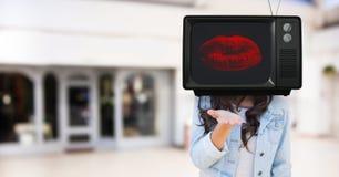 Fille envoyant un baiser avec la tête de TV Photo stock