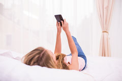 Fille envoyant un texte sur le lit à la maison dans la chambre à coucher images stock