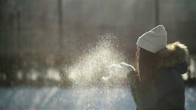 Fille espiègle appréciant Sunny Weather Outside froid La femme étonnante dans le profil souffle sur des flocons de neige de ses m banque de vidéos