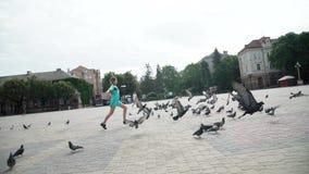 Fille espiègle courant parmi des pigeons sur le secteur de ville 4K clips vidéos
