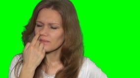 Fille espiègle de femme faisant les expressions du visage - nez de cueillette avec le doigt banque de vidéos