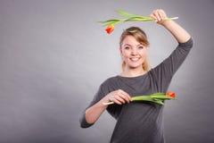 Fille espiègle ayant l'amusement avec des tulipes de fleurs Photographie stock libre de droits