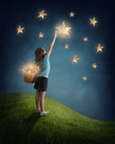 Fille essayant d'attraper une étoile Photographie stock