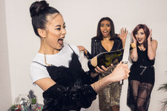 Fille essayant d'ouvrir la bouteille de champagne avec le couteau tandis que ses amis se tenant sur le fond Photo libre de droits