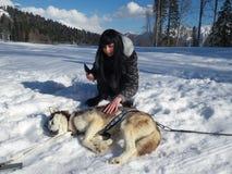 Fille essayant de réveiller le chien enroué se situant dans la neige Photographie stock libre de droits
