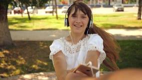 Fille et ami dansant main dans la main Mouvement lent la fille dans des écouteurs sourit et avec le téléphone dansant et tournant banque de vidéos