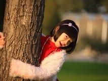 Fille et arbre asiatiques heureux Image libre de droits