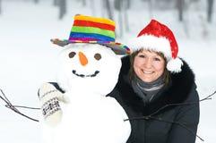 Fille et bonhomme de neige heureux en hiver Images stock