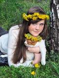 Fille et chat couverts de taches de rousseur en guirlandes de fleurs Image libre de droits