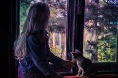 Fille et chat regardant par la fenêtre Photo stock
