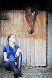 Fille et cheval équestres dans l'écurie Photos libres de droits