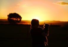 Fille et chien appréciant observant le coucher du soleil au-dessus des montagnes dans le pays Photos libres de droits