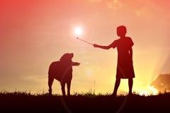 Fille et chien de silhouette Photographie stock libre de droits