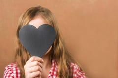 Fille et coeur noir d'ardoise La fille établit une physiognomie, des grimaces et un coeur pour une inscription Concept de Saint-V photo stock