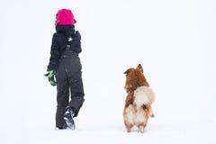 Fille et crabot dans la neige Images libres de droits