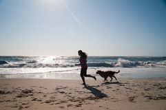 Fille et crabot fonctionnant sur la plage Photos libres de droits