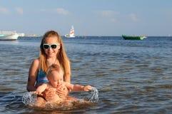 Fille et enfant en bas âge ayant l'amusement en mer Image stock