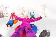 Fille et enfants glissant en bas de la colline sur des tubes Images libres de droits